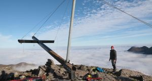 The cross on the summit of Carrauntoohil - cut down over a week ago - was replaced by a group of volunteers early on Saturday morning. Photograph: Valerie O'Sullivan