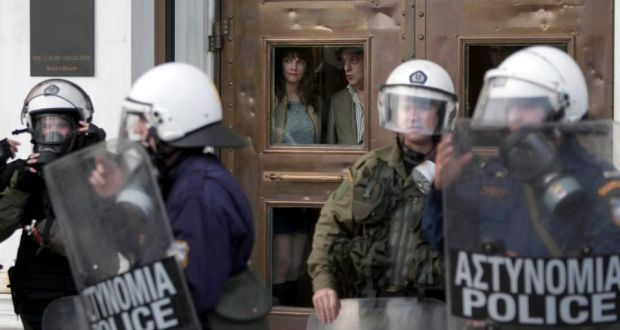 Tourists look out from behind the door of  a hotel in  Athens during a demonstration remembering  the victims of a 1973 uprising against the military junta last month. Photograph: Yannis Kolesidis/Epa