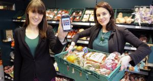 Aoibheann O'Brien and Iseult Ward, co-founders of foodcloud, a company taking an innovative approach to minimising food waste by supermarkets and other retailers. Aoibheann is pictured with a donation basket from Tesco in Ringsend, while Iseult displays the company's phone app.Photograph: DAVE MEEHANMONDAY 17TH FEBRUARY 2014