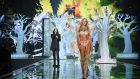 Victoria's Secret model Candice Swanepoel walks the runway past  Hozier during the 2014 Victoria's Secret fashion show at Earl's Court exhibition centre yesterday in London. Photograph:  Dimitrios Kambouris/Getty Images