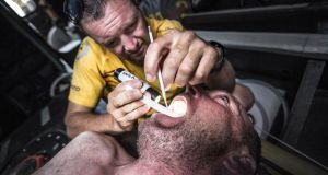 Dr Wendy (Phil) Harmer repairs a sensitive tooth on Justin Slattery with temporary filling work in the bow onboard. Photograph:  Matt Knighton/Abu Dhabi Ocean Racing/Volvo Ocean Race via Getty Images