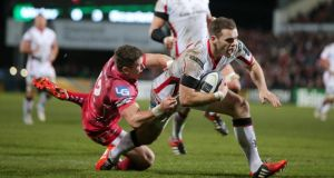 Ulster's Darren Cave scores a try despite the tackle of Scarlets' Scott Williams during the European Rugby Champions Cup match at  Kingspan Stadium in Belfast. Photograph:  Darren Kidd/Inpho/Presseye
