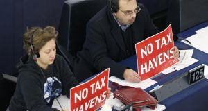 MEPs from the European United Left group protest in the European Parliament over tax avoidance.
