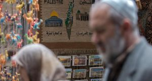Palestinians pass a wall decoration for sales in the Moslem Quarter of the Old City in Jerusalem. Photograph: Jim Hollander/EPA