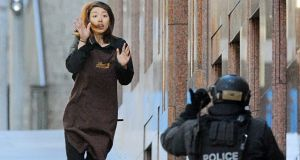 An employee manages to escape from the Lindt Chocolate cafe in Martin Place, Sydney,  after an armed terrorist took dozens of people hostage.  Crying women were seen holding up a black Islamic flag up to the window.  It is estimated that up to 50 people could be inside.  Photograph: EPA/JOEL CARRETT
