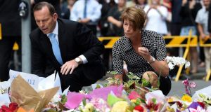 Australian Prime Minister Tony Abbott and his wife Margie join thousands of Sydney residents to lay flowers at a memorial near the Lindt chocolate cafe in Martin Place following the  siege. Photograph: EPA