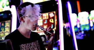 A casino patron exhales vapour from an e-cigarette in Las Vegas. A study carried out by the internationally regarded Cochrane Library has found a third of long-term smokers were able to cut their cigarette consumption in half by using e-cigarettes. Photograph: Sandy Huffaker/New York Times