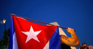 An anti-Castro cuban exile carries a Cuban flag during protests in Little Havana in Miami. Photograph: Reuters/Carlos Barria