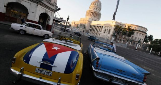 A car with a Cuban flag parked near  the Cuban Capitol in Havana. The Cuban revolution has survived through a combination of welfare provision and selective repression as the equal distribution of scarce resources meets the iron fist of state power. Photograph: Enrique De La Osa/Reuters