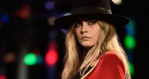 Cara Delevingne sports a 1970s looks at Saint Laurent's Paris Fashion Week show. Photograph: Pascal le Segretain/Getty