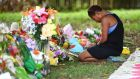 A mourner at a floral tribute near a house in which eight children were stabbed to death in the Cairns suburb of Manoora, Australia, on Sunday. Photograph