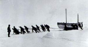 Sir Ernest Shackleton's crew haul the James Caird, after their ship the Endurance broke up in the ice in 1916, with Shackleton looking on. Photograph: PA
