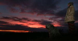 Shirley Finn with her dog Nin, watches the sunset at Dowth, in Co Meath on Saturday ahead of the Winter Solstice. Photograph: PA