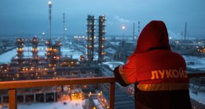 An employee looks out over an oil refinery  in Nizhny Novgorod, Russia. The drop in oil prices is driving a sharp recession in the country. Photograph: Andrey Rudakov/Bloomberg