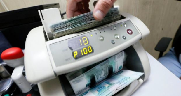 The Russian currency is down some 40 per cent against the dollar this year.An employee uses a machine while counting Russian ruble banknotes at a private company's office in Krasnoyarsk, Siberia. Photograph: Ilya Naymushin/Reuters