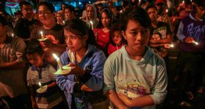 Indonesians hold candles during a vigil for the victims of the crashed AirAsia airplane in Surabaya, East Java, Indonesia. Photograph: Fully Handoko/EPA.