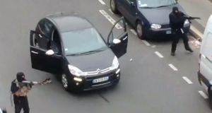 Gunmen flee the offices of French satirical newspaper Charlie Hebdo in Paris, in this still image taken from amateur video shot on January 7, 2015, and obtained by Reuters.