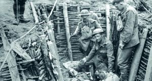 Irish Guards with a wounded man in a trench near Wytschaete, Belgium. Photograph: From Father Browne's First World War by E E O'Donnell (Messenger Publications)