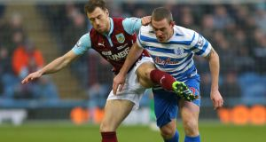 QPR defender Richard Dunne challengBurnley's Ashley Barnes  during the  Premier League match at Turf Moor. Photograph: Dave Thompson/PA