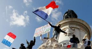 "People hold aloft  a poster translating as ""Quick: more democracy everywhere against barbarism"" take part in a solidarity rally  (Marche Republicaine) in  Paris on January 11th, 2015. Photograph: Youssef Boudlal/Reuters"