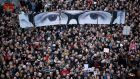 "People hold panels to create the eyes of late Charlie Hebdo editor Stephane Charbonnier, known as ""Charb"", as French citizens take part in a solidarity march (Marche Republicaine) in the streets of Paris on Sunday. Photograph: Reuters/Yves Herman"
