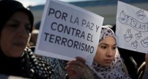 "A Muslim protester holds a placard reading ""Islam"" and another one holds one reading ""For peace and against terrorism"" during a demonstration outside Atocha Station in Madrid against the recent Paris Charlie Hebdo attacks . Photograph: Pablo Blazquez Dominguez/Getty Images"