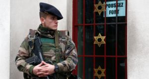 A French soldier secures the access to a Jewish institution in Neuilly-sur-Seine, in western Paris on Tuesday, as part of the  security plan put in place after last week's attacks by Islamist militants. France will deploy 10,000 soldiers on home soil  and post almost 5,000 extra police officers to protect sensitive  sites after the killing of 17 people by Islamist militants in Paris last week. Photograph: EPA