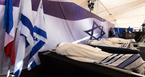 The four coffins of Jews killed in the Paris kosher supermarket, Yoav Hattab, Yohan Cohen, Francois-Michel Saada and Phillipe Braham, lined up in front of a large flag of Israeli with its Star of David as prime minister Benjamin Netanyahu delivers his eulogys at the funeral in the cemetery on Tuesday, before the bodies, wrapped in prayer shawls, are removed and taken to graves for burials. Photograph: EPA