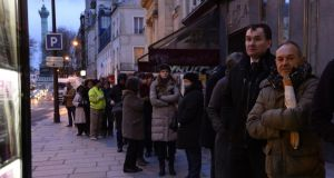 People wait outside a newsagents kiosk in Paris on Wednesday. Photograph: AFP/Getty/Bertrand Guaybertrand