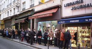 People queue outside a Paris newsagent's yesterday as the latest edition of satirical magazine Charlie Hebdo goes on sale. Photograph: AFP/Getty Images