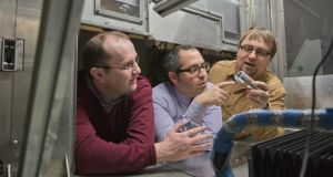 Prof Rocco Lupoi (centre) examines a product sample of his 3D printer and special spray device made at TCD with assistant professors (left) Shaun McFadden and Anthony Robinson. Photograph: Brenda Fitzsimons