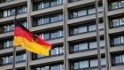 A German flag flies in front of the Bundesbank headquarters in Frankfurt. Photographer: Ralph Orlowski/Bloomberg