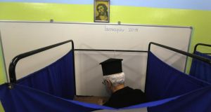 A Greek orthodox priest casts his vote inside a polling booth in an elementary school in Athens. Photograph: Yannis Behrakis/Reuters