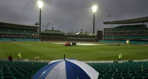 A small number of fans wait in hope for the rain to stop and play to begin during the One Day International cricket match between Australia and India in Sydney. Photograph: Craig Golding/Getty Images