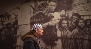 Holocaust survivor Igor Malicky (90) pauses for thought as he tours an exhibition inside the former Auschwitz I concentration camp ahead of commemorations marking the 70th year since its liberation. Photograph: Christopher Furlong/Getty Images