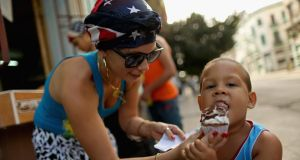 The United States flag is appearing in small ways in the clothing worn by Cubans, like the scarf worn by Gydis Ricardo Vargas  as she gives her son Wisin Abascal Ricardo some ice cream  in Havana, Cuba. Photograph:  Chip Somodevilla/Getty Image