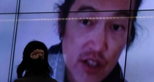 A woman looks at television screens displaying a news report  about Japanese journalist Kenji Goto.  IS militants said on Saturday  they had killed Mr Goto. Photograph: Reuters