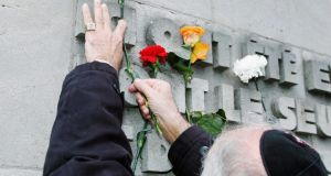 A World War II veteran places a flower on the memorial wall during a commemoration service in the former concentration camp Bergen-Belsen in northern Germany. Photograph: Getty Images