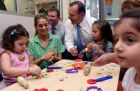 Australian Prime Minister Tony Abbott reacts as he watches children playing during his visit to the Little Pines Childcare Centre in Sydney, Australia. Abbott announced that the 1.5 per cent levy on the nation's 34-hundred biggest companies will be invested in child care instead of the dropped parental leave scheme. (Photograph: Paul Miller/EPA)