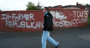 A man walks past graffiti relating to the Boston College tapes on the Falls Road, west Belfast last year. Photograph: Paul McErlane/EPA