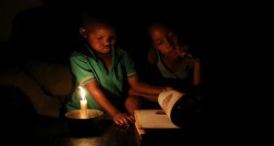 Studying by candle light during load shedding in Soweto.  Photograph: Siphiwe Sibeko/Reuters