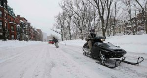 A snow-mobile pulls a man on snow board on Commonwealth Avenue in Boston, Massachusetts. Photoghraph: Brian Snyder /Reuters