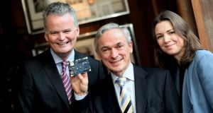 Mark Redmond of the American Chamber of Commerce Ireland, Richard Bruton, Minister for Jobs, Enterprise & Innovation, and Laura Mahoney of the Royal Irish Academy with an Intel Quark chip on a Galileo board, designed in Ireland. It is an example of world-class research innovation conducted in Ireland as a result of US FDI