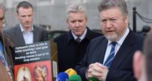 Minister for Children James Reilly with an example of how plain packaging would look. As health minister, he refused to meet a delegation of tobacco industry leaders in Government Buildings. Photograph: Dara Mac Dónaill