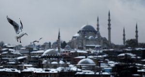 A seagull flies close to the Suleymaniye Mosque during heavy snow fall in Istanbul on Wednesday. Istanbulites woke up to find the famed minarets and domes of the historic city's skyline layered in snow after a heavy fall overnight. Photograph: Ozan Koze/AFP/Getty Images.