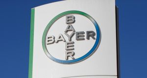 The Bayer AG logo stands on a sign outside of the company's headquarters ahead of a news conference to announce the drugmaker's earnings in Leverkusen, Germany, on Friday, Feb. 28, 2014. Bayer raised its forecast for peak sales of new drugs such as the blood thinner Xarelto even as fourth-quarter results and the revenue outlook for this year missed analyst estimates. Photographer: Jasper Juinen/Bloomberg