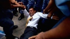 Former Maldives President Mohamed Nasheed is dragged into the country's justice building having been arrested after a court said he might flee the country to avoid facing terrorism charges. Video: Zayn Inax/Reuters