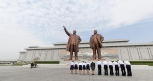 North Korean workers bow before  statues of the President Kim Il Sung and the General Secretary Kim Jung Il at the Mansudae Grand Monument in Pyongyang, North Korea