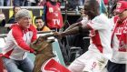 Anthony Ujah yanking on the horns of Hennes, team mascot of FC Koln, which is sponsored by  supermarket chain Rewe