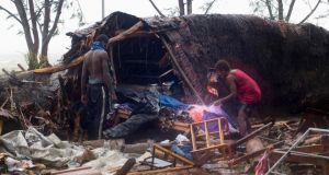 Local residents look through the remains of a small shelter in Port Vila, the capital city of the Pacific island nation of Vanuatu On Saturday. Winds of up to 340 km/h hit the country as  category 5 cyclone named Pam was unleashed. Photograph: UNICEF Pacific/Handout via Reuters.